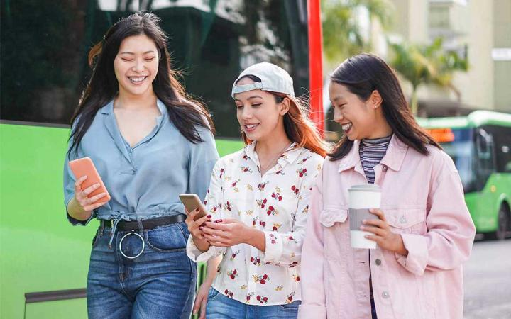 3 girls looking at smartphones and laughing in front of a bus