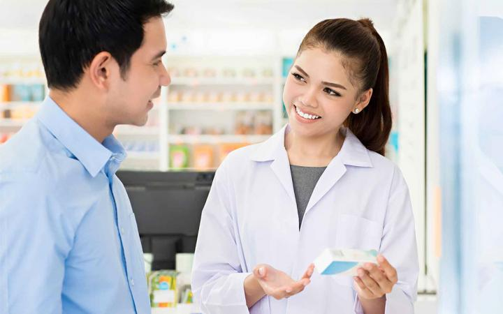 Young man and female pharmacist looking at a medicine packet